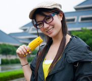 Girl eating corn. Close-up outdoor portrait of young beauty woman eating corn-cob Stock Image