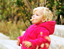 Girl eating corn curls Stock Image