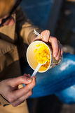 Girl eating corn. Girl eating corn out of a paper Cup with a plastic spoon Royalty Free Stock Photo