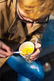 Girl eating corn. Girl eating corn out of a paper Cup with a plastic spoon Stock Image