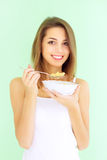 Girl eating cornflakes with. Smiling girl eating cornflakes with a green background Stock Photo