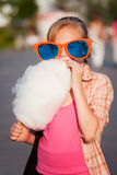 Happy teen girl in sunglasses eating cotton candy walking in city street Royalty Free Stock Photos
