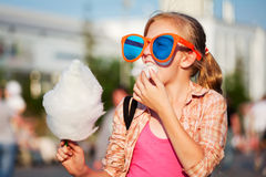 Fashion teen girl eating cotton candy walking in city street