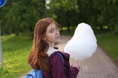 Girl eating cotton candy. At the park Stock Photo