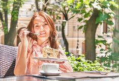 Girl is eating a dessert (cake) in the café. Royalty Free Stock Images