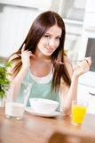 Girl eating dieting cereals and citrus juice. Portrait of the girl eating dieting muesli with milk and orange juice sitting at the kitchen table Stock Photography