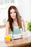 Girl eating dieting muesli and citrus juice. Portrait of the girl eating dieting cereals with milk and orange juice sitting at the kitchen table Royalty Free Stock Images
