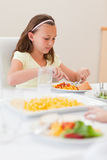 Girl eating at dinner table Stock Images