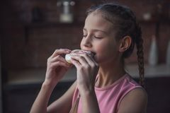 Girl eating donut. Cute girl is tasting donut with closed eyes while standing in kitchen Royalty Free Stock Image