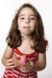 Girl eating doughnut licking lips Stock Photo