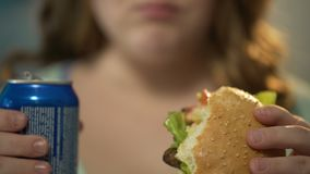 Girl eating fatty burger and drinking sugary soda from can, overeating junk food. Stock footage stock video