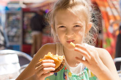 Girl eating French fries and a hamburger sandwich Stock Photos