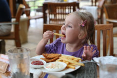 Girl eating French fries. Stock Images