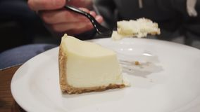 Girl eating fresh cheesecake with a fork while sitting in the kitchen or in a cafe. Slow motion.