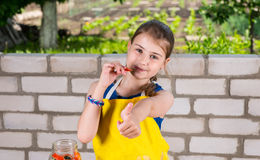 Girl Eating Fresh Peppers and Giving Thumbs Up Stock Photography