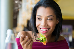 Girl eating fresh salad Stock Images