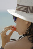 Girl eating fruit on the beach Royalty Free Stock Photo