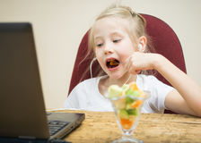 Girl eating fruit cocktail next to the laptop. Royalty Free Stock Photography