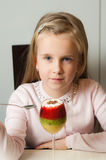 Girl eating fruit mousse from a glass Royalty Free Stock Photography