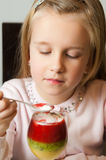 Girl eating fruit mousse from a glass Stock Photography