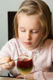 Girl eating fruit mousse from a glass Royalty Free Stock Image
