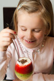 Girl eating fruit mousse from a glass Stock Photos