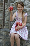 Girl is eating fruits. A seven year old girl is eating apples Stock Photos