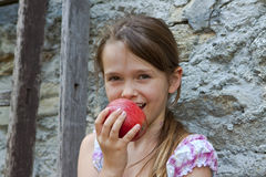 Girl is eating fruits. 7 year old girl is eating an apple Royalty Free Stock Photos
