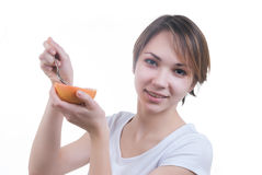 Girl eating grapefruit by the spoon Royalty Free Stock Image