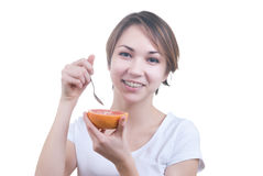 Girl eating grapefruit by the spoon Royalty Free Stock Photo