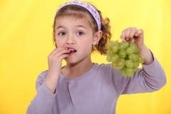 Girl eating grapes. Royalty Free Stock Photos