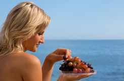 Girl eating grapes at the beach by the sea. royalty free stock images