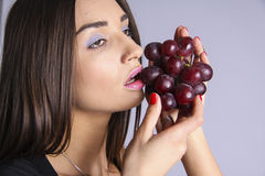 Girl eating grapes Stock Photography