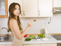 Girl eating a greek salad in the kitchen. Girl with a salad Royalty Free Stock Image