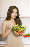 Girl eating a greek salad in the kitchen. Girl with a salad Stock Photos