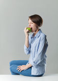 Girl eating a green apple Stock Images