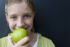 Girl eating a green apple Royalty Free Stock Photos