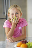 Girl Eating Green Apple At Kitchen Counter Royalty Free Stock Image