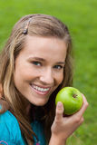 Girl eating a green apple in a park Stock Photography