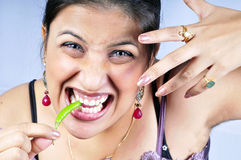 Girl eating green chilly Stock Image
