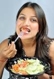 Girl eating green salad Royalty Free Stock Image
