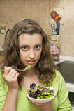 Girl eating green salad Royalty Free Stock Photography