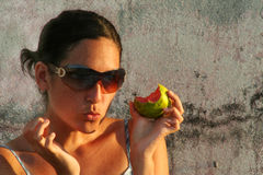 Girl eating a guava fruit. Girl with chewing expression holds a bitten guava fruit Stock Image