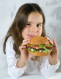 Girl eating hamburger. Young girl eating hamburger happily Stock Photography