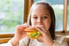 Girl eating hamburger Stock Photos