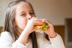Girl eating hamburger Royalty Free Stock Photos