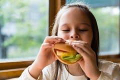 Girl eating hamburger Stock Images