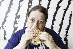 Girl eating hamburger Stock Photography