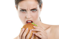 Girl eating hamburger on white background. dissatisfied face Royalty Free Stock Images