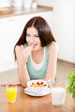 Girl eating healthy cereals and strawberry Royalty Free Stock Image